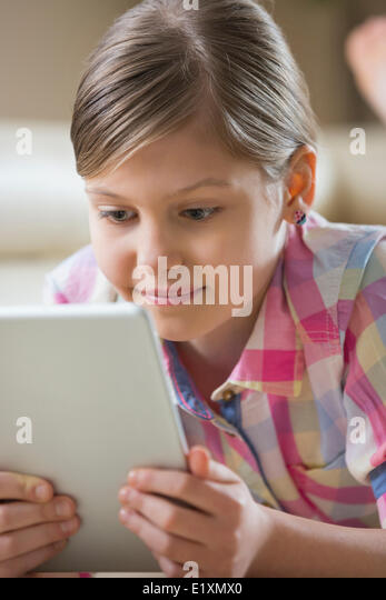 Close-up of girl using digital tablet at home - Stock Image