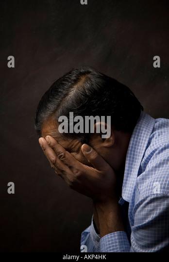 Indian man head in hands - Stock Image