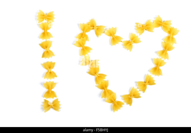 pasta farfalle arranged heart shape isolated on white - Stock Image