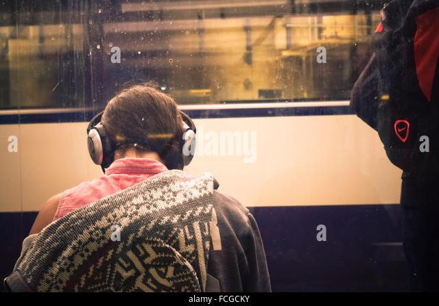Young woman back with headphones on listening to music. In the background the car of a train in motion. London, - Stock Image