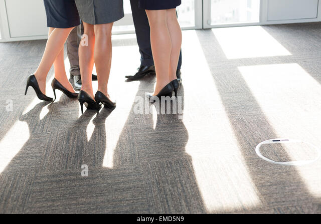 Business people standing in circle, low section - Stock Image