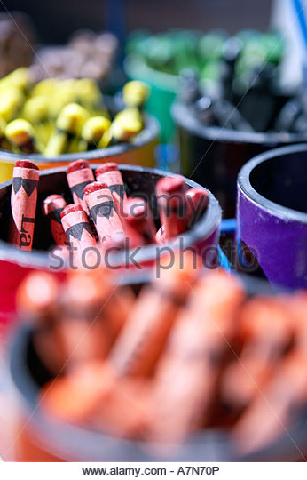 Pots of multi coloured crayons in rows close up still life differential focus full frame - Stock Image