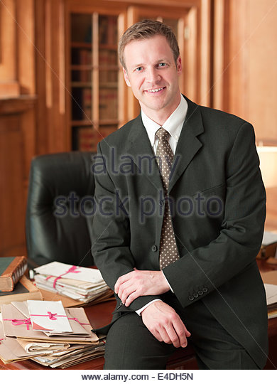 Smiling lawyer leaning on desk in office - Stock Image