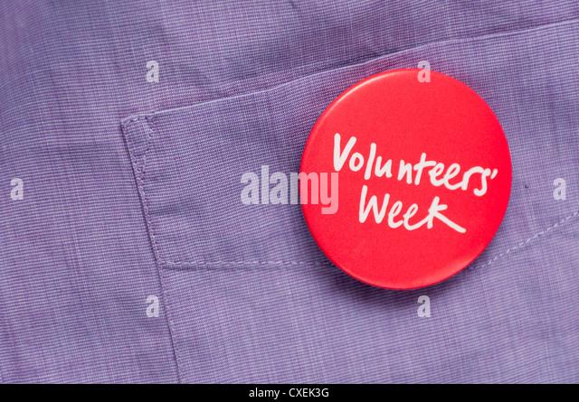 Volunteer promoting volunteering wearing volunteers week badge - Stock Image