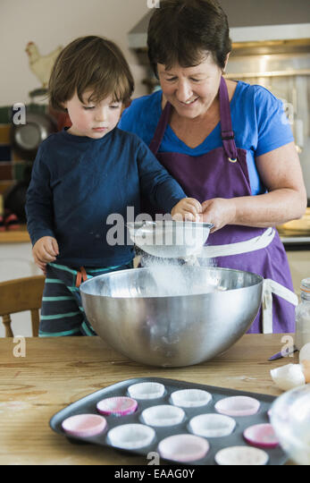 A woman and a child cooking at a kitchen table, making fairy cakes. - Stock Image