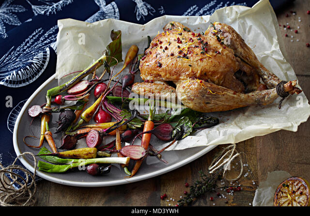 Roast chicken and vegetables on serving tray - Stock Image
