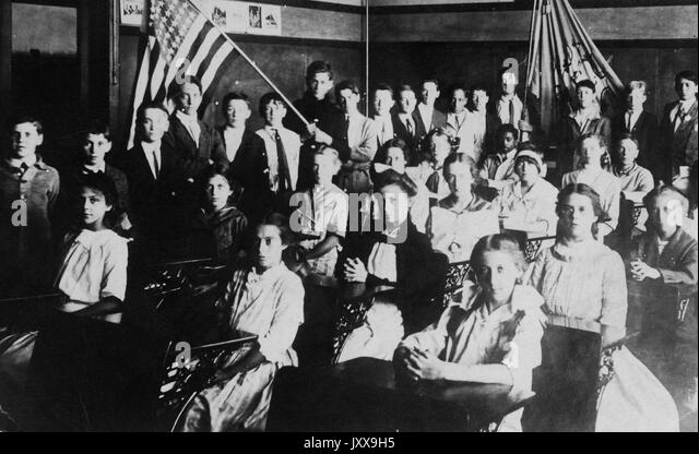 Landscape full length shot of Caucasian students indoors seated at desks, neutral facial expressions, one student - Stock Image