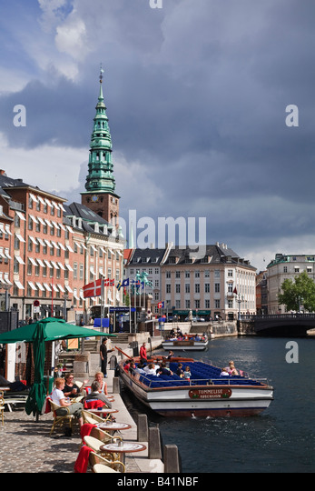 Canal tour boat and view towards Nikolaj Kirke from Gammel Strand, Copenhagen, Denmark - Stock Image