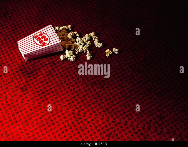 Spilled carton of popcorn on cinema carpet - Stock Image