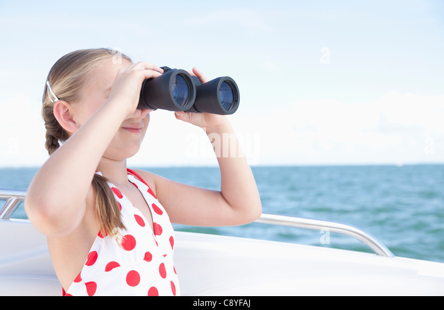 USA, Florida, St. Petersburg, Girl (10-11) on yacht looking through binoculars - Stock Image