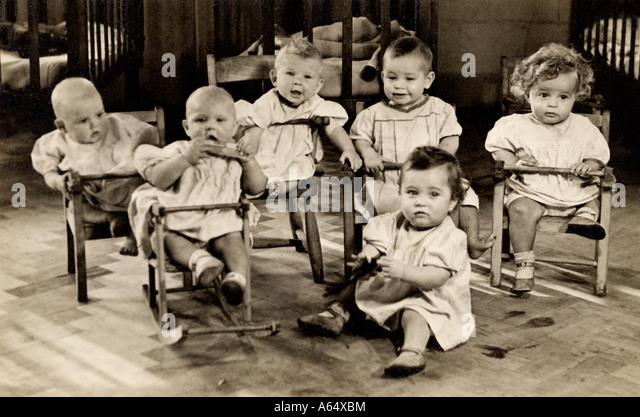 Unusual image of six babies in a nursery in East London in the early 1900's possibly in a Barnardo's orphanage, - Stock Image