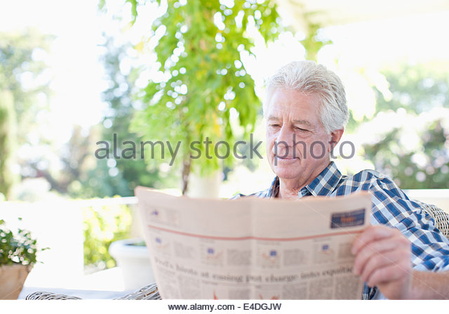 Senior man reading newspaper on patio - Stock Image