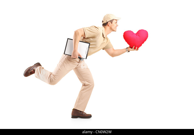 Delivery boy in a rush delivering red heart shaped pillow isolated on white background - Stock Image