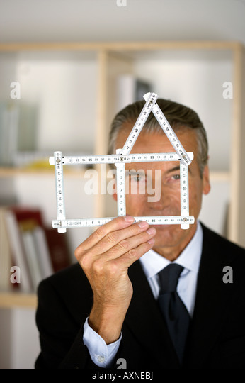 Senior businessman holding a model of a house - Stock Image