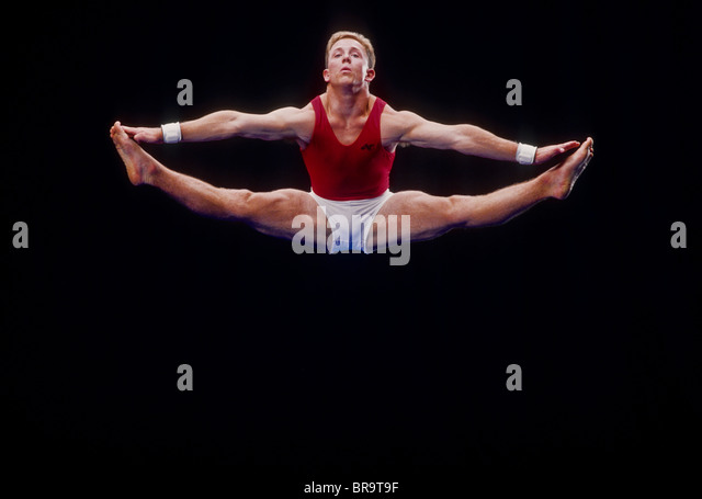 Male gymnast performing on the floor exercises. - Stock Image
