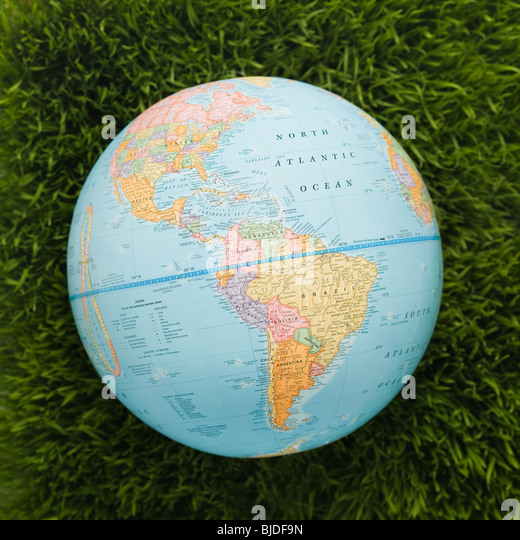 Globe against background of grass. - Stock Image
