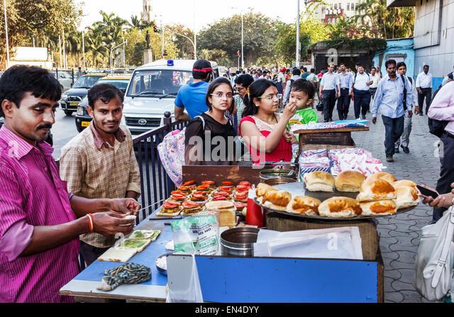 Mumbai India Asian Karmaveer Bhaurao Patil Marg road street food vendor man woman mother girl child - Stock Image