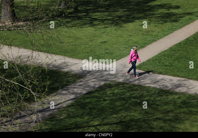 Woman at a crossroad junction in a park, deciding which way to go. - Stock Image