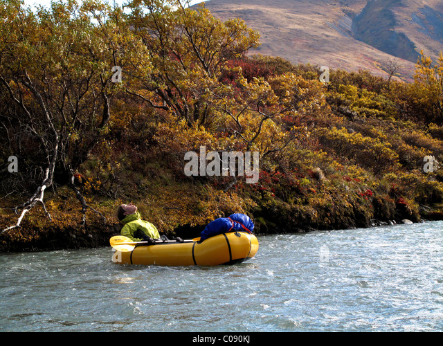 Woman packrafts down the Sanctuary River in Denali National Park, Interior Alaska, Autumn - Stock Image