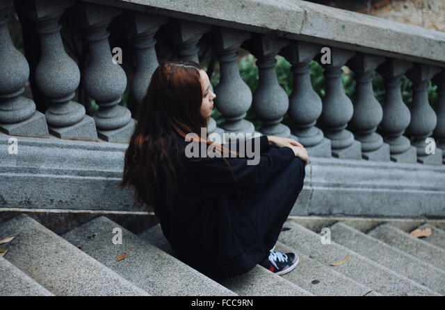 High Angle View Of A Thoughtful Teenage Girl Sitting On Stairs - Stock Image