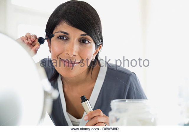 Beautiful mature woman applying mascara - Stock Image