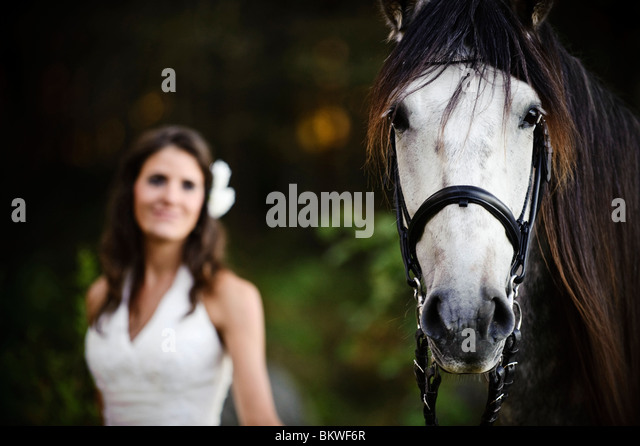 Woman standing beside horse - Stock Image