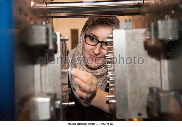 Close up of woman working on machinery - Stock-Bilder