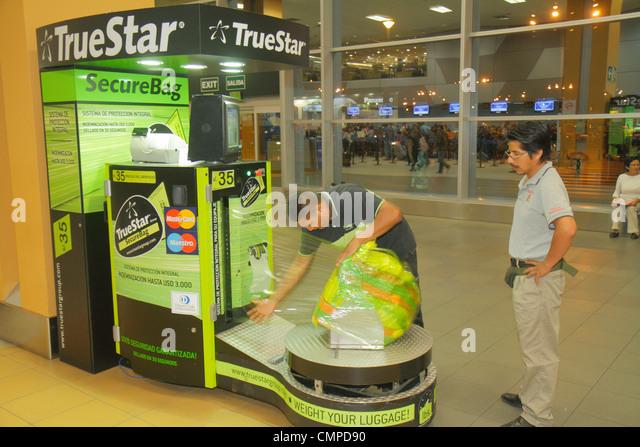 Peru Lima Jorge Chávez International Airport LIM aviation terminal departures Hispanic man passenger luggage - Stock Image