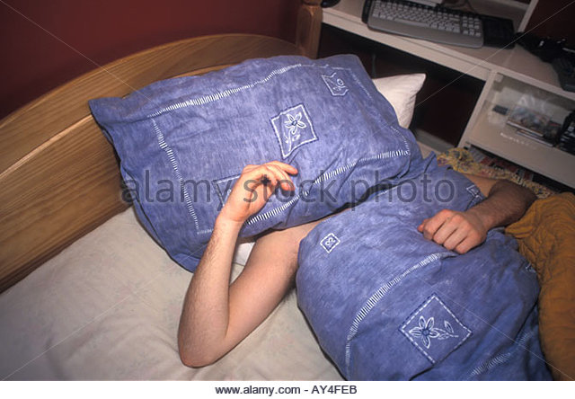 16 year old teenage boy asleep in bed in the morning does not want to get up UK - Stock-Bilder