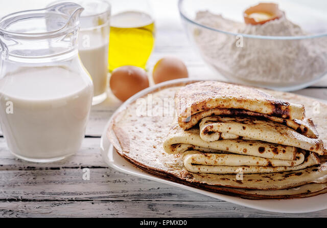 Close-up of crepes Stack and ingredients for cooking on a wooden table. Rustic style. Selected focus. - Stock Image