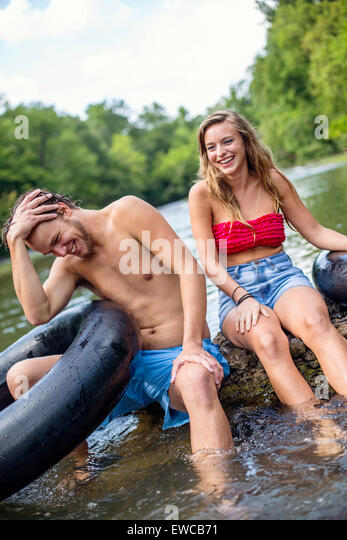 A young couple tubes down a river. - Stock Image