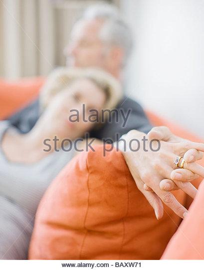 Mature couple laying on sofa holding hands - Stock-Bilder