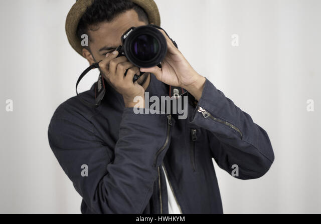 Man in jacket and hat clicking a picture with a dslr camera - Stock Image