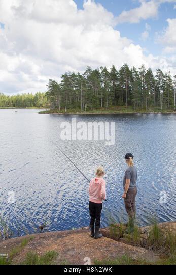 Mature woman and girl (12-13) fishing in lake - Stock Image