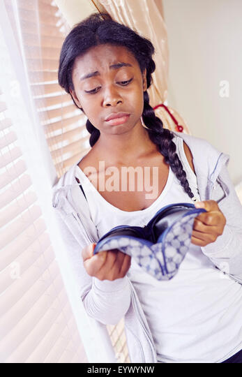 Girl looking in purse - Stock Image