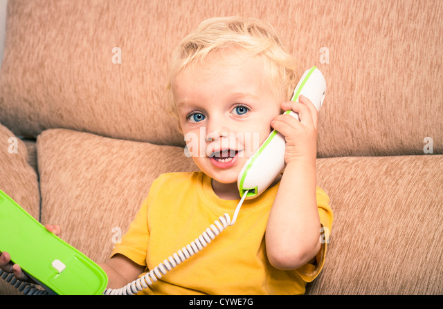 Happy cute adorable child boy on the phone. - Stock Image