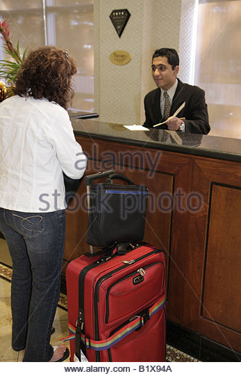 Little Rock Arkansas The Peabody Little Rock hotel lobby Asian man woman guest luggage front desk job customer service - Stock Image