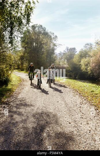 Front view of family on rural road riding bicycles - Stock Image