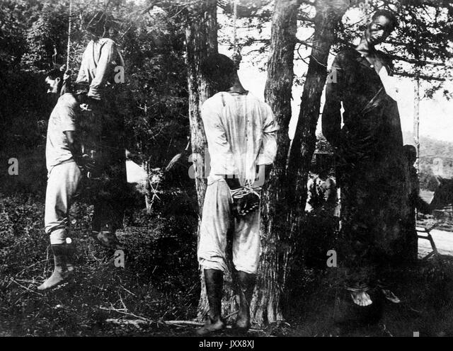 Four African American men hang from trees, their hands bound behind their backs, apparent victims of lynchings, - Stock Image