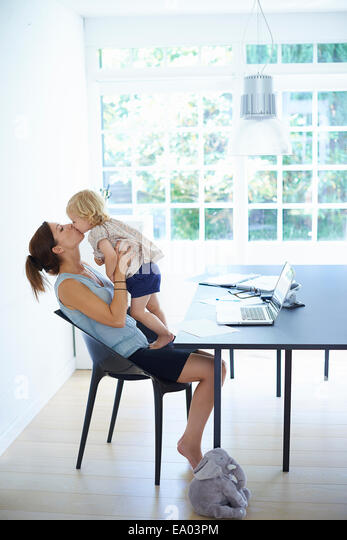 Mid adult woman holding up and kissing toddler daughter - Stock Image