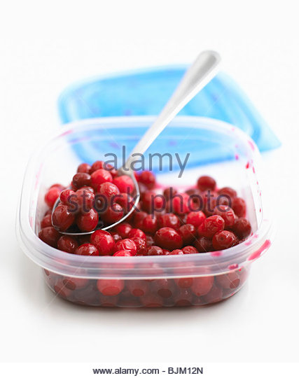 Cooked cranberries with spoon in a plastic box - Stock Image