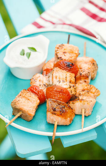 Grilled salmon kebabs with cherry tomatoes and garlic sauce - Stock Image