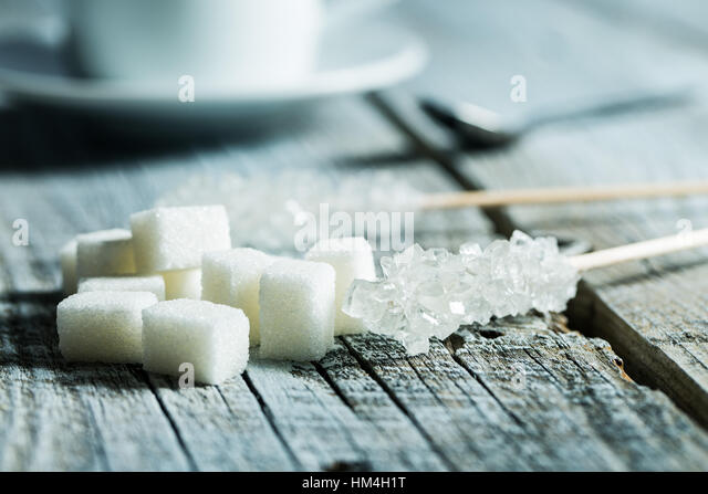 Crystallized sugar on wooden stick and sugar cubes on wooden table. - Stock Image