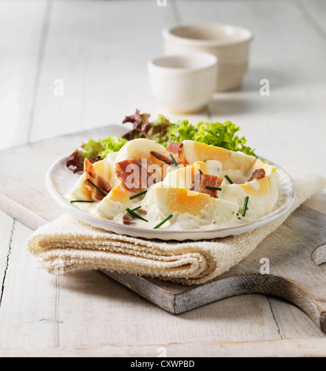 Plate of eggs, bacon and salad - Stock Image