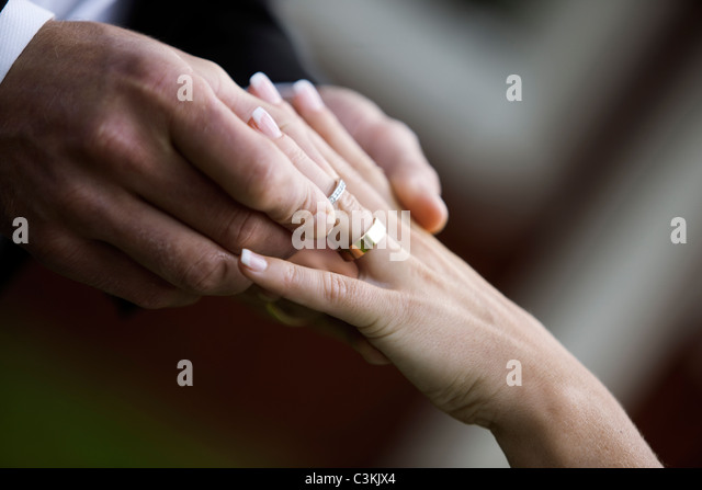 Bridegroom and bride putting on rings - Stock Image