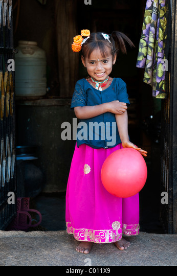 Smiling happy pretty rural Indian village girl holding a balloon in the doorway to her home. Andhra Pradesh, India - Stock Image