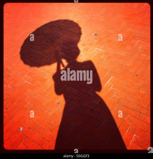 Silhouette shadow of female holding a parasol. - Stock Image