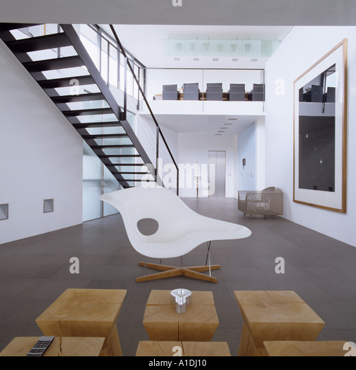 Eames chair in front of Philippe Starck wooden stools in modern apartment with mezzanine - Stock Image