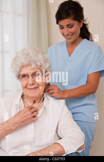 USA, Illinois, Metamora, Female nurse helping senior woman to put pearl necklace - Stock Image