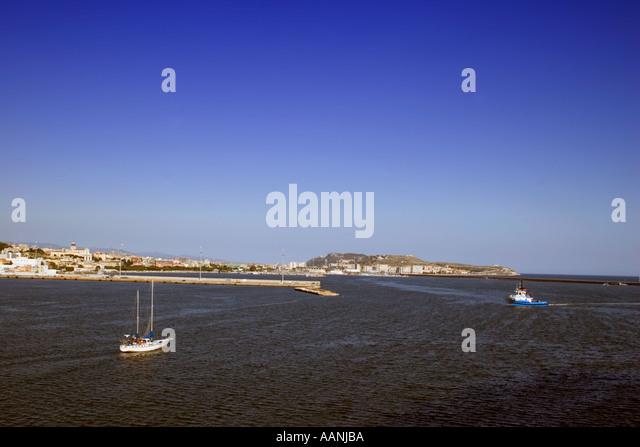 Cagliari skyline and Yacht Sardinia tug yacht sailing boat sail sailboat Cagliari Sardinia skyline town city skyline - Stock Image